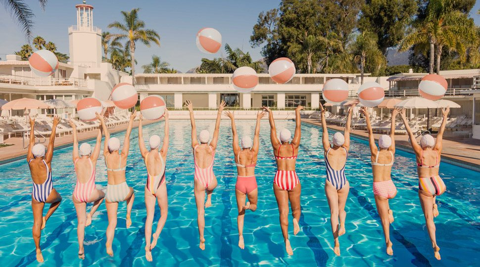 Women jumping into a pool