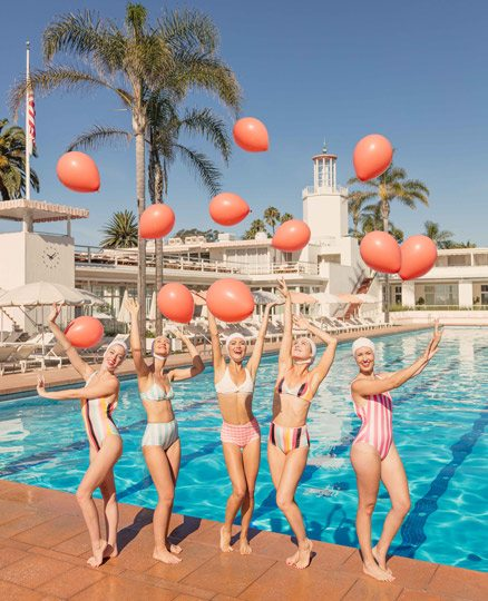 Five women holding balloons poolside