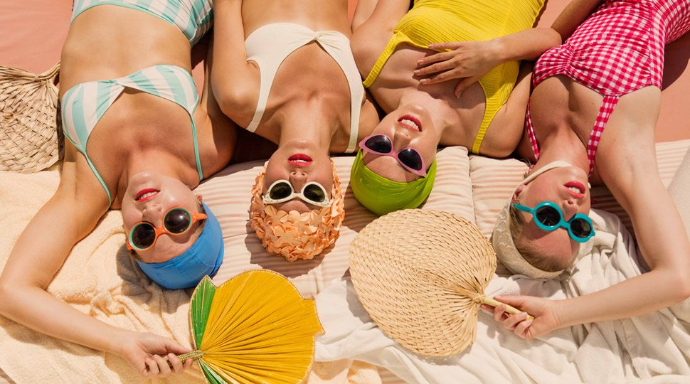 Four women sunbathing with fans