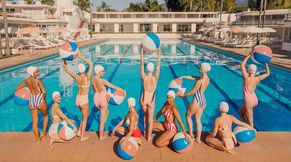 Women holding beach balls poolside