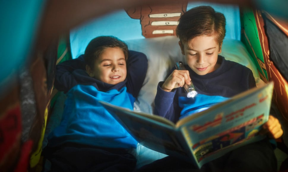 Two kids reading in bed