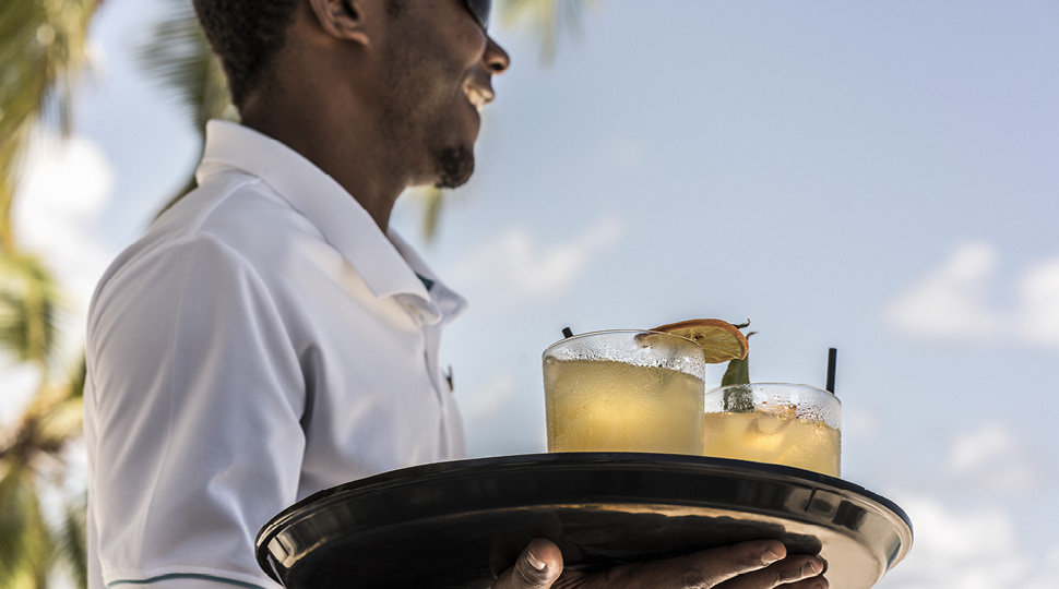 Waiter carries a tray of cocktails
