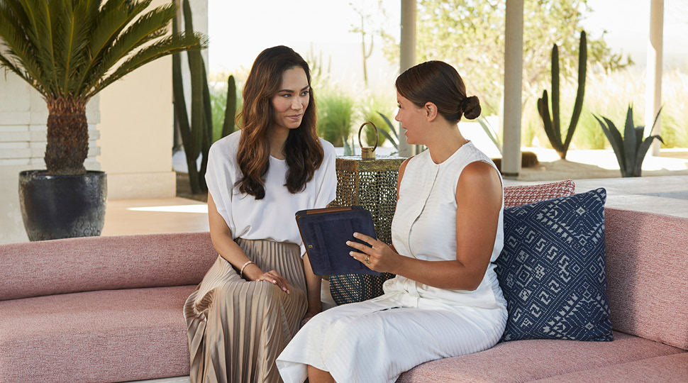 Two women sit on a couch looking at a digital tablet