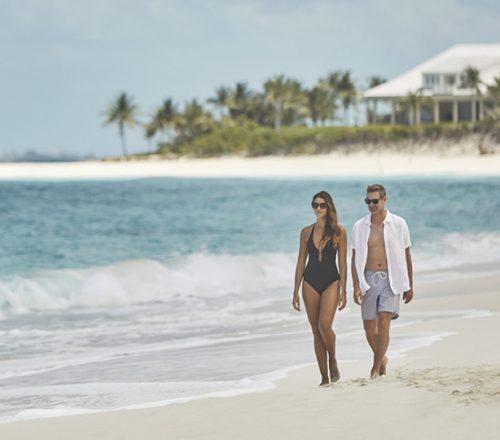 A couple walks along a white sandy beach