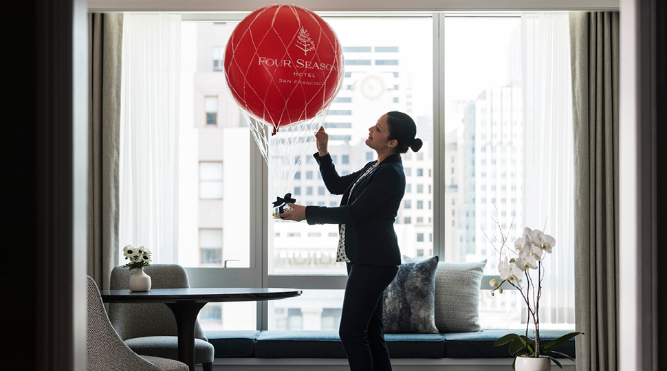 Woman in hotel room with balloon