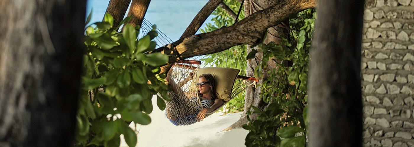 Woman lounges in a beachside hammock