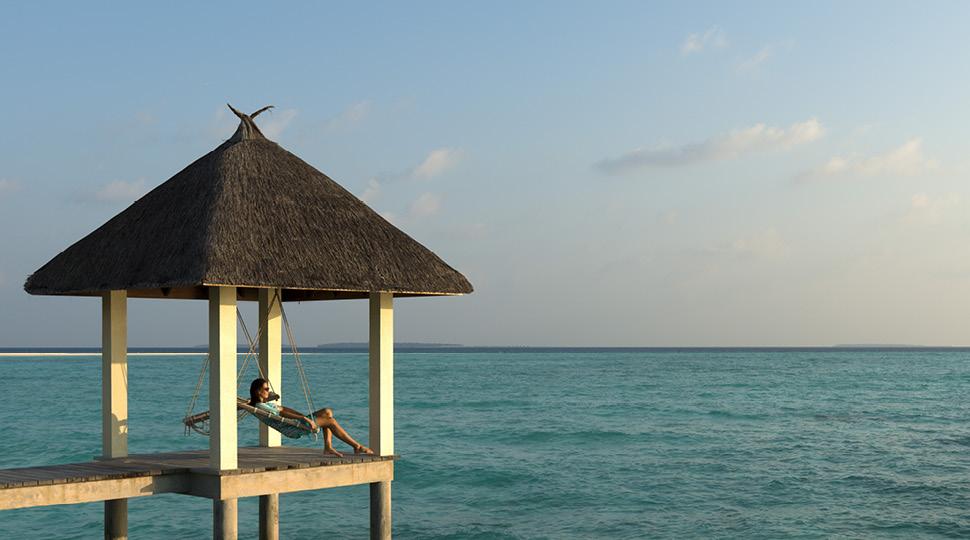 Woman sits in swing under a gazebo overlooking the ocean