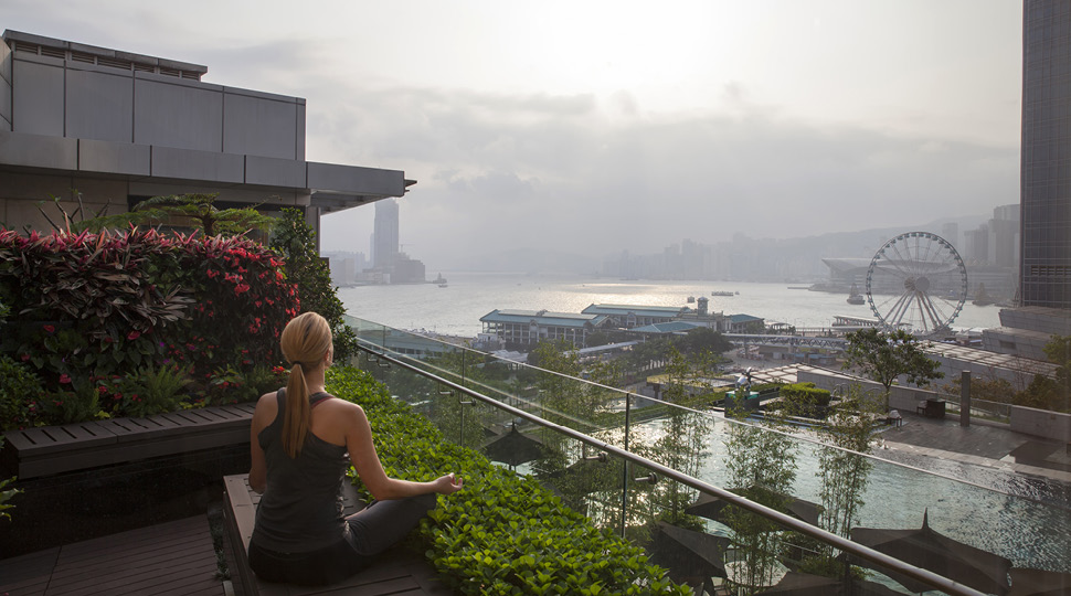 Woman mediating on a rooftop overlooking a harbour and ferris wheel