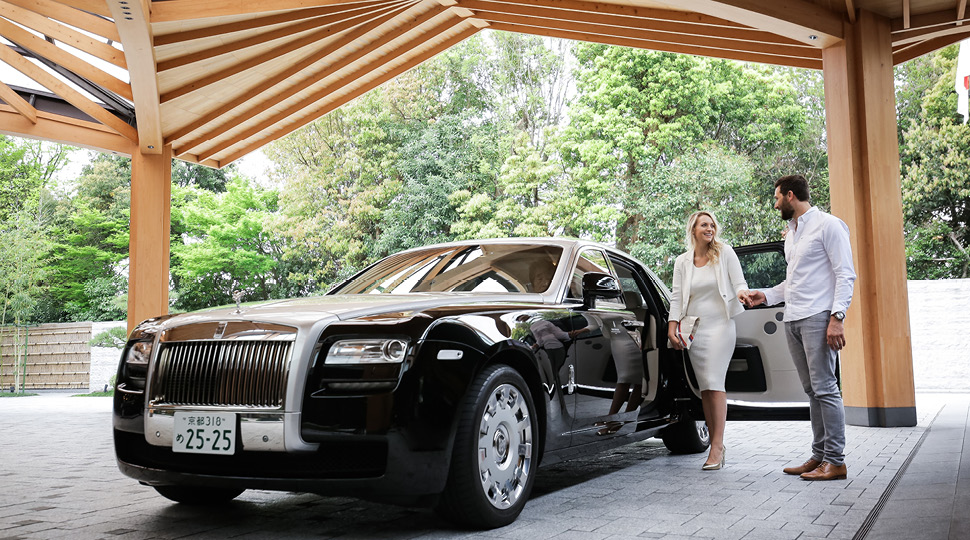 A woman in a white dress and a man in a white button-up shirt step out of a Rolls Royce