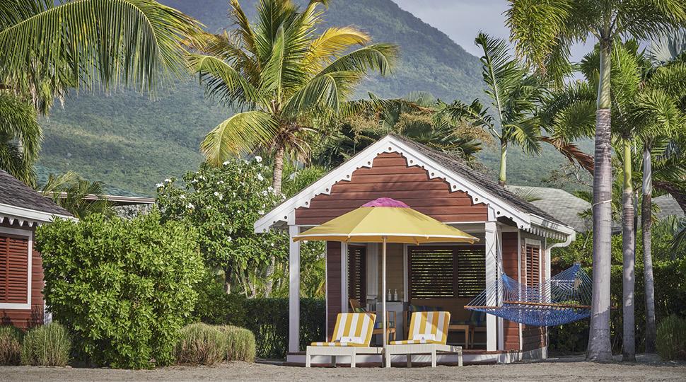 Empty beach cabana with yellow chairs and yellow umbrella
