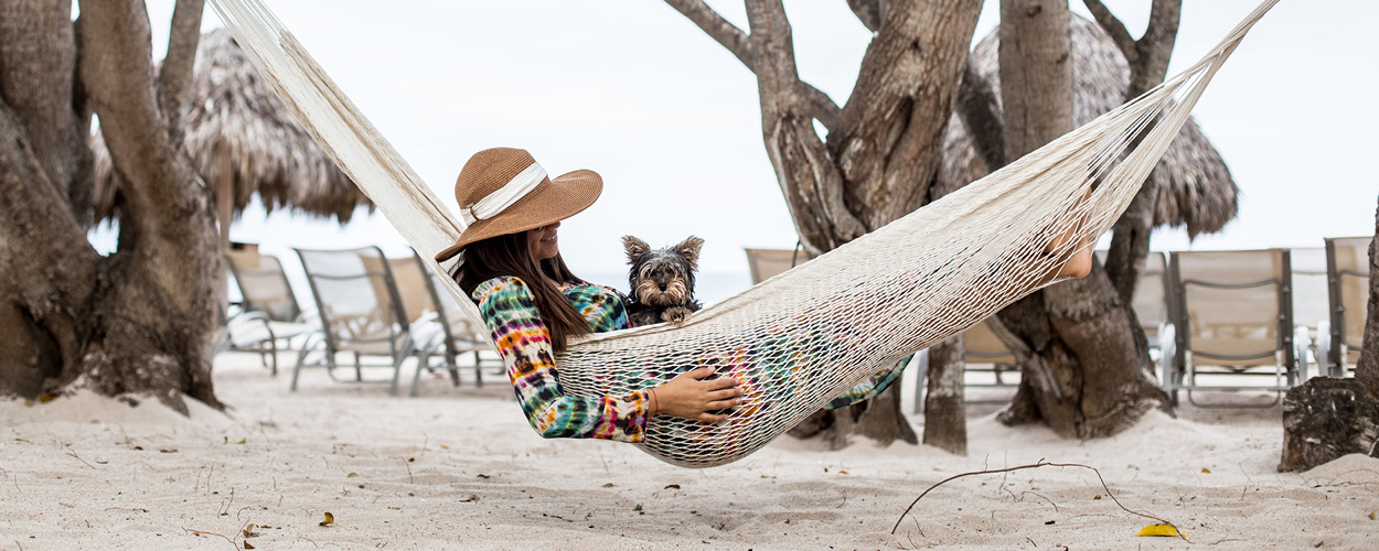 A woman in a straw hat sits in a hammock on the beach with a small dog in her lap