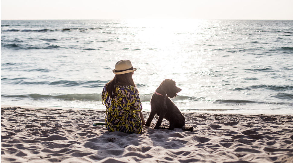 A woman in a straw hat sits with a black dog on the beach