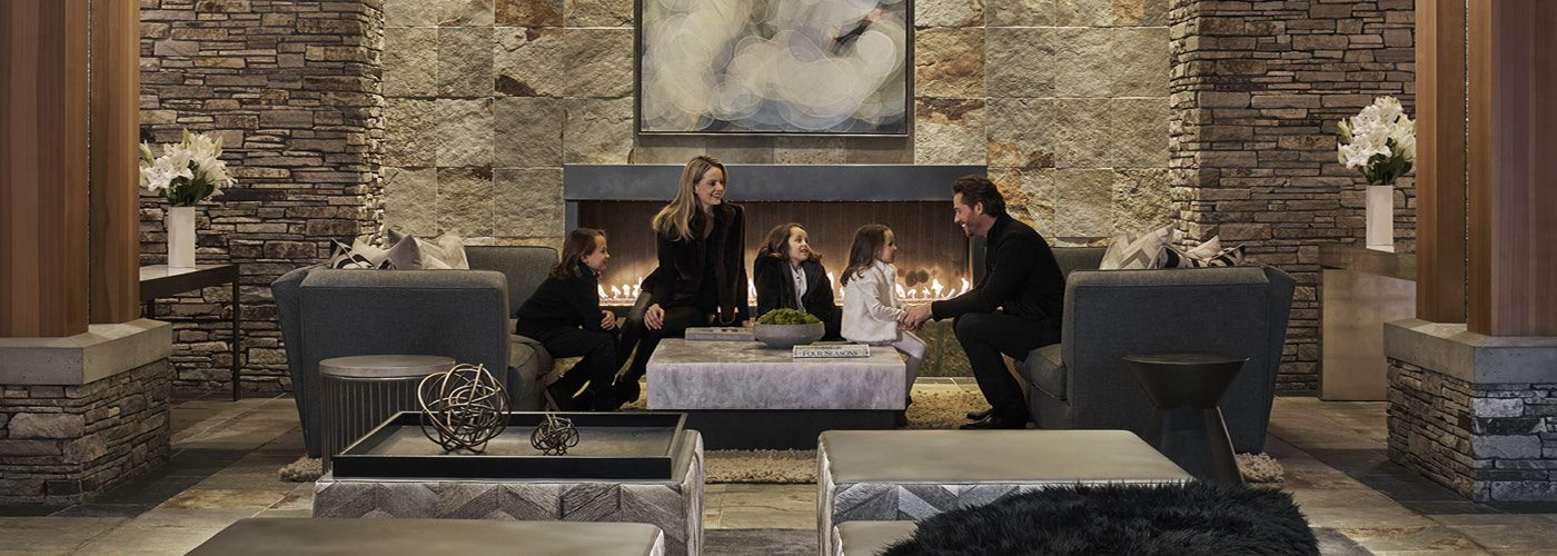 A family sits in a living room with a fireplace in the background