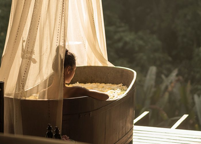A woman lounges in a canopied bathtub overlooking the jungle