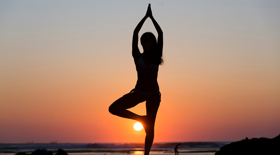 Silhouette of a woman holding a yoga pose overlooking the ocean and sunset