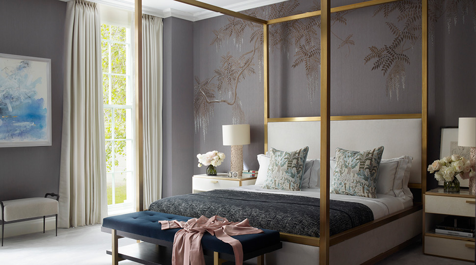 A king bed with a gold frame and printed tropical pillows with a pink robe draped on a teal ottoman at the foot of the bed