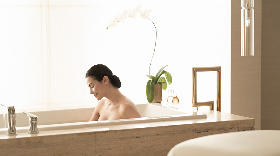 A woman bathes in a large bathtub