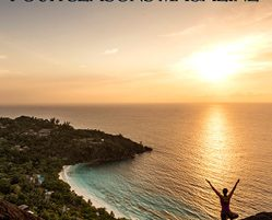 Silhouette of a woman holding a yoga pose on the edge of a mountain overlooking the ocean and sunset