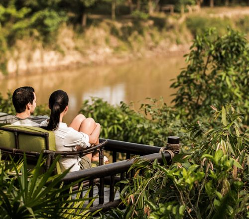 A couple sits on an outdoor couch overlooking the jungle