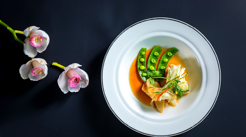 Grouper on a white plate with yams and spring onion