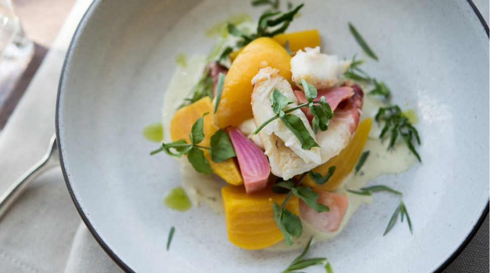 Beet & dungeoness crab salad on a white plate